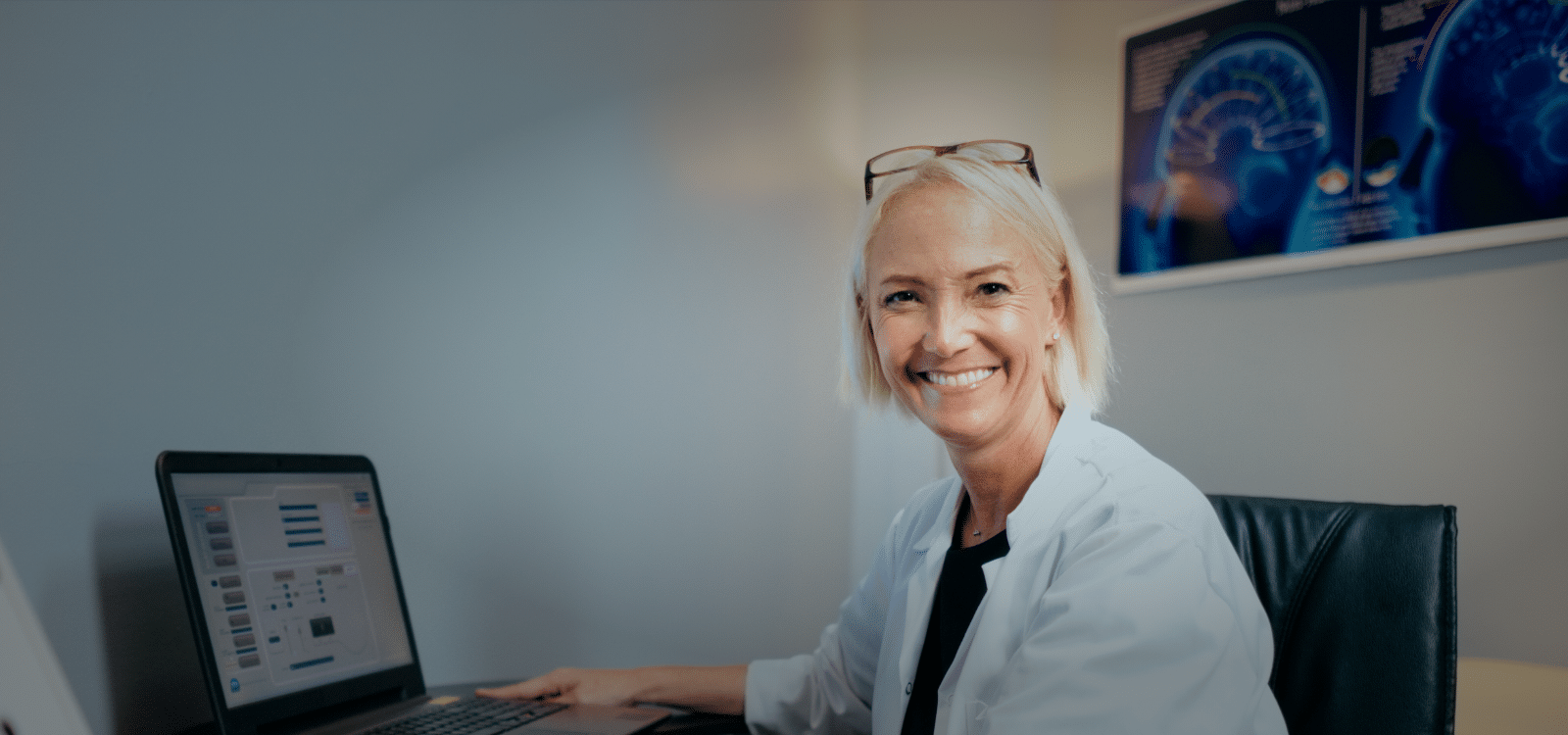 smiling woman doctor looking at patient file on a laptop