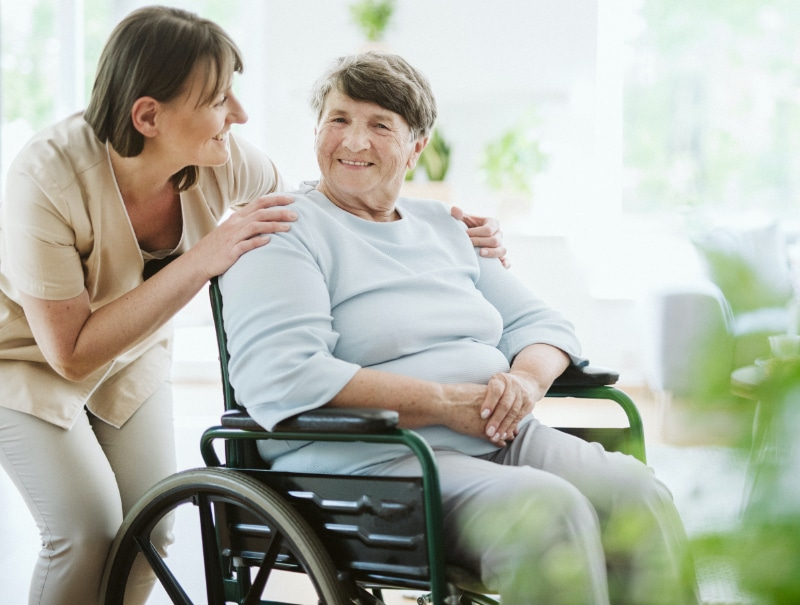 woman standing behind a woman seated in a wheelchair