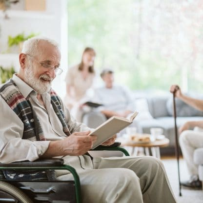 smiling elderly man seated in a wheelchair reading a book