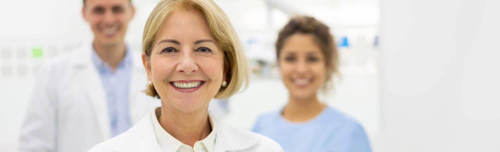 close-up of a female doctor standing in front of two medical assistants