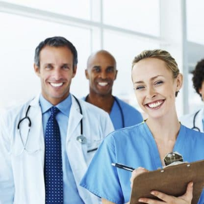 smiling woman with clipboard standing with three smiling medical coworkers in background