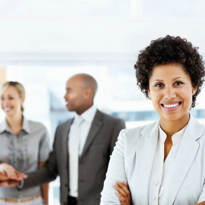 smiling woman standing in front of three celebrating coworkers