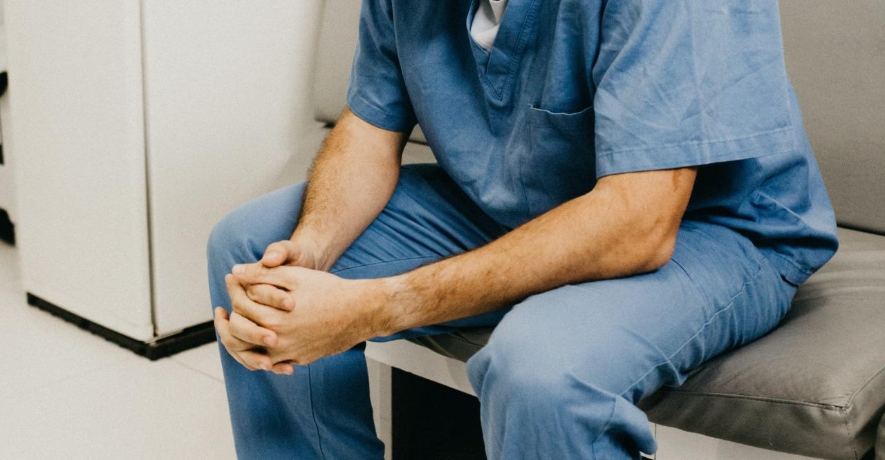 Man in scrubs holding hands