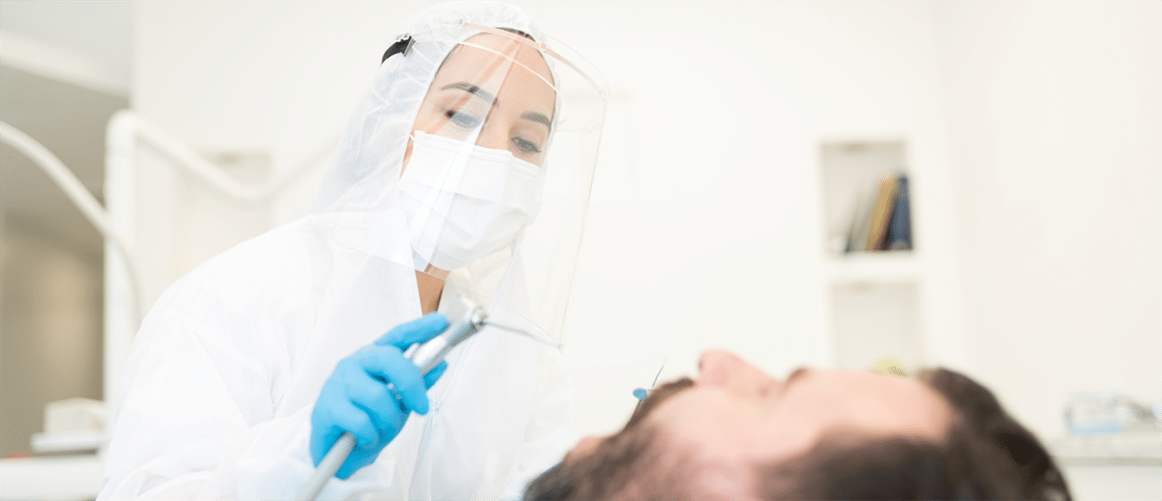 Dentist leaning over patient with mouth open