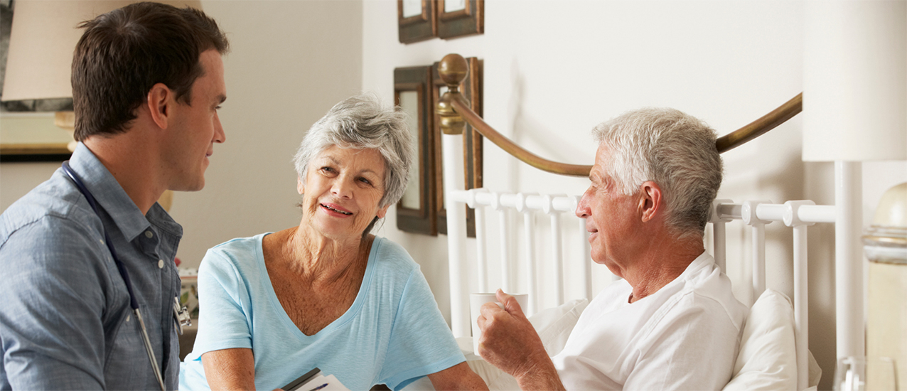 Home health worker talking to older couple
